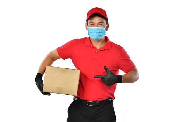 Glücklicher junger asiatischer lieferbote in der roten uniform, medizinische gesichtsmaske, schutzhandschuhe tragen pappkarton in den händen, die auf weiß lokalisiert werden. zusteller geben paketversand. sichere lieferung