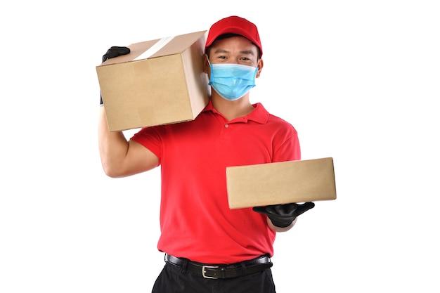 Glücklicher junger asiatischer lieferbote in der roten uniform, medizinische gesichtsmaske, schutzhandschuhe tragen pappkarton