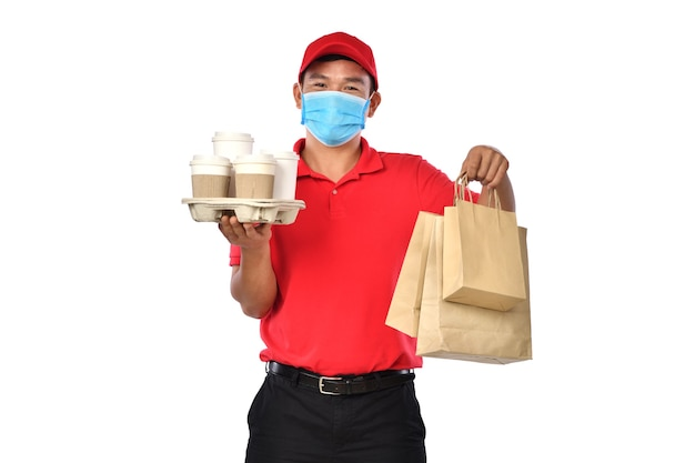 Glücklicher junger asiatischer lieferbote in der roten uniform, medizinische gesichtsmaske tragen taschen von essen und trinken in den händen lokalisiert auf weißem hintergrund