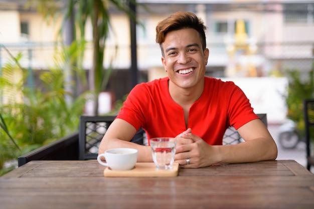 Glücklicher junger asiatischer mann, der an der kaffeestube draußen lächelt