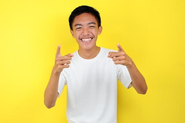 Glücklicher junger asiatischer mann, der auf die kamera lächelt, isoliert auf gelb