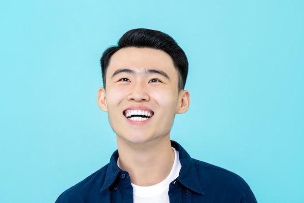 Glücklicher junger asiatischer mann, der aufwärts lächelt und schaut