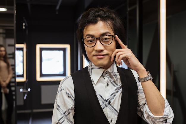 Glücklicher junger asiatischer mann, der brille trägt kamera betrachtet.