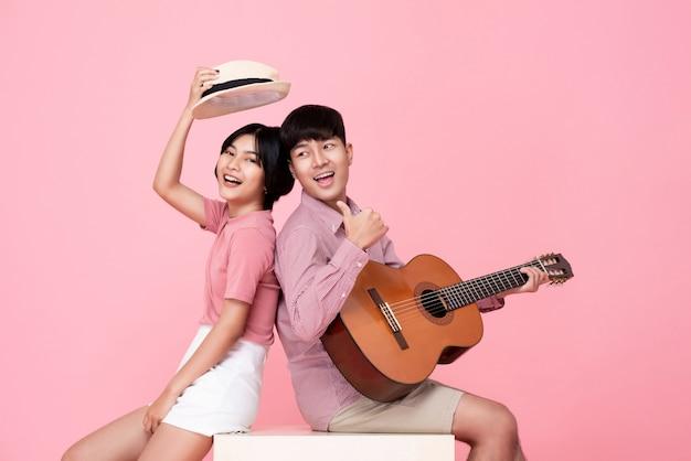 Glücklicher junger asiatischer mann, der gitarre spielt und mit seiner freundin singt
