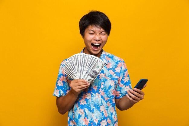 Glücklicher junger asiatischer mann, der isoliert über gelbem raum steht, der geld hält und handy verwendet.