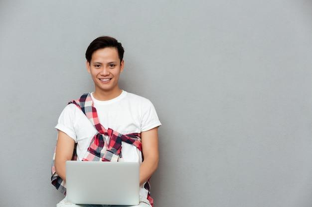 Glücklicher junger asiatischer mann, der laptop benutzt