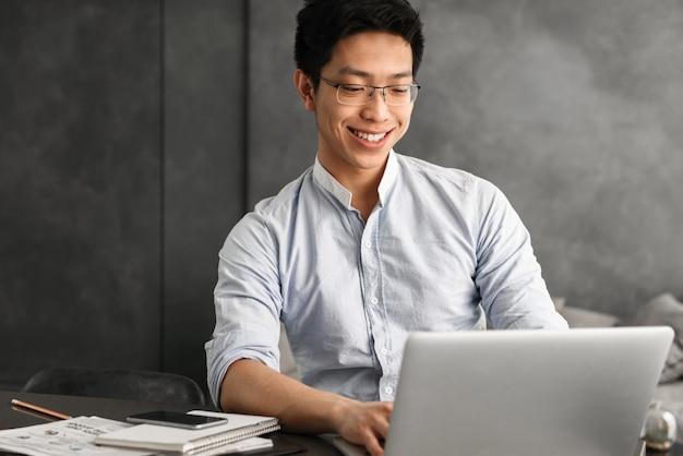 Glücklicher junger asiatischer mann, der laptop-computer verwendet