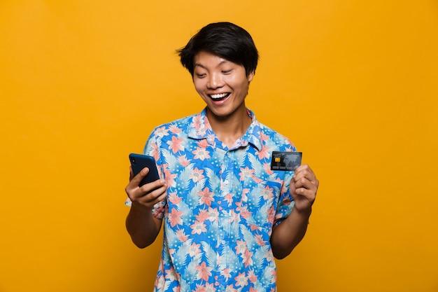 Glücklicher junger asiatischer mann, der lokalisiert über gelbem raum unter verwendung der handy-haltekreditkarte steht.