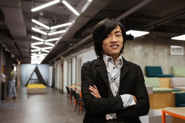 Glücklicher junger asiatischer mann gekleidet in formelle kleidung. coworking-konzept.
