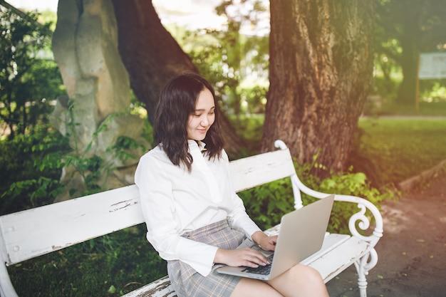 Glücklicher junger asiatischer student in einem park, der am laptop arbeitet