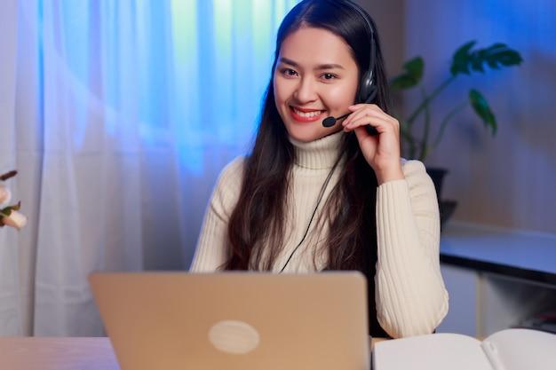 Glücklicher junger asiatischer weiblicher ausbilder oder betreiber, der headset trägt, das nachtarbeit online macht