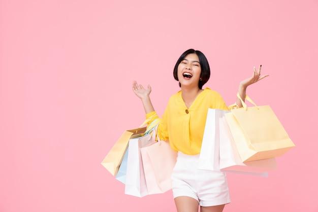 Glücklicher junger asiatischer weiblicher tragender pastell färbte einkaufstaschen mit beiden armen