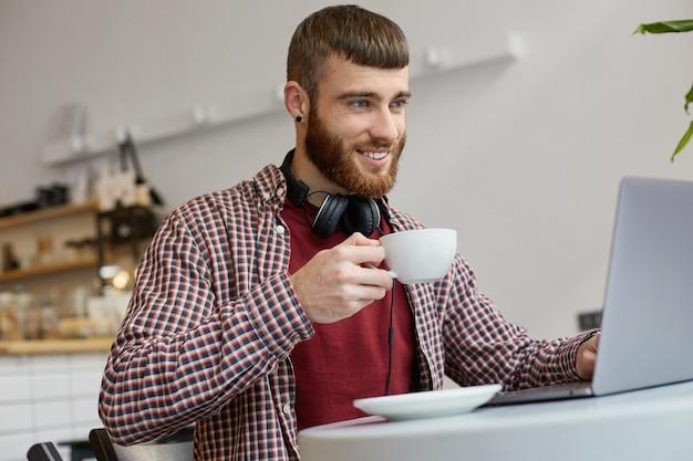 Glücklicher junger attraktiver bärtiger mann des ingwers, der an einem laptop arbeitet, während er in einem café sitzt, genießt die arbeit, lächelt und trinkt kaffee, trägt in der grundkleidung.