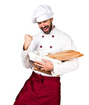Glücklicher junger bäcker hält brot