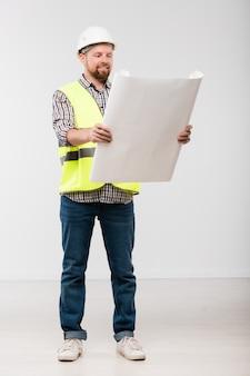 Glücklicher junger bärtiger baumeister im weißen helm, in den jeans, im karierten hemd und in der gelben weste, die blaupause vor der kamera betrachten