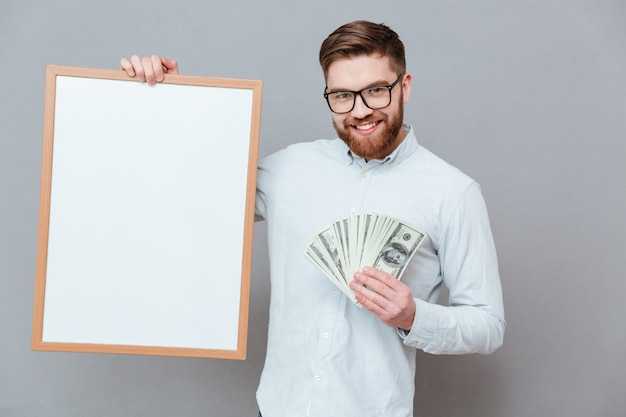 Glücklicher junger bärtiger geschäftsmann, der copyspace-brett und geld hält