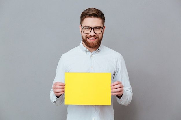 Glücklicher junger bärtiger geschäftsmann, der leeres papier hält