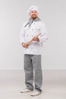 Glücklicher junger bärtiger koch in der uniform, die hölzernen nudelholz hält, während er isoliert vor kamera steht
