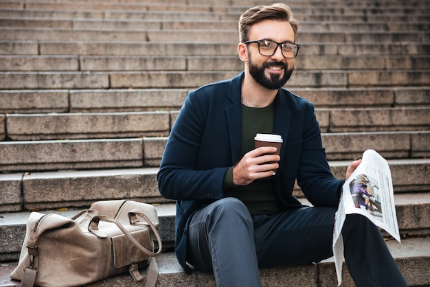 Glücklicher junger bärtiger mann, der draußen auf stufen sitzt