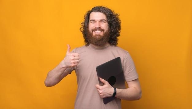 Glücklicher junger bärtiger mann lächelnd, der laptop hält und daumen oben geste über gelb zeigt