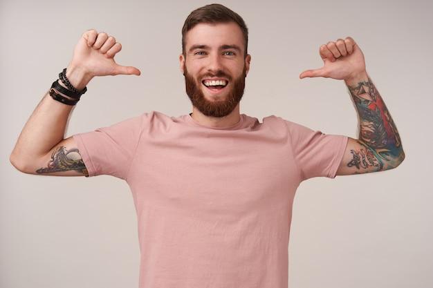 Glücklicher junger bärtiger mann mit tätowierungen und kurzem haarschnitt, der freizeitkleidung trägt, während er auf weiß posiert, freudig schaut und mit erhobenen daumen auf sich selbst zeigt