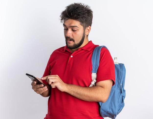 Glücklicher junger bärtiger student kerl in rotem poloshirt mit rucksack, der smartphone hält, das nachrichten lächelt, die über weißem hintergrund stehen