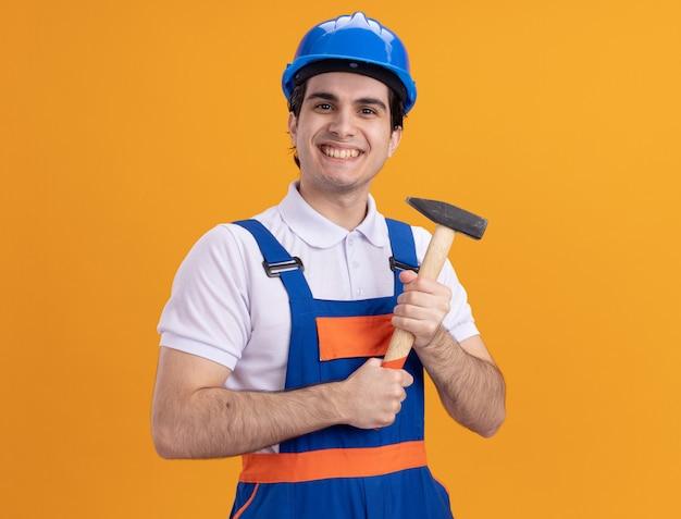 Glücklicher junger baumeistermann in der bauuniform und im sicherheitshelm, der hammer hält, der vorne lächelnd fröhlich über orange wand steht