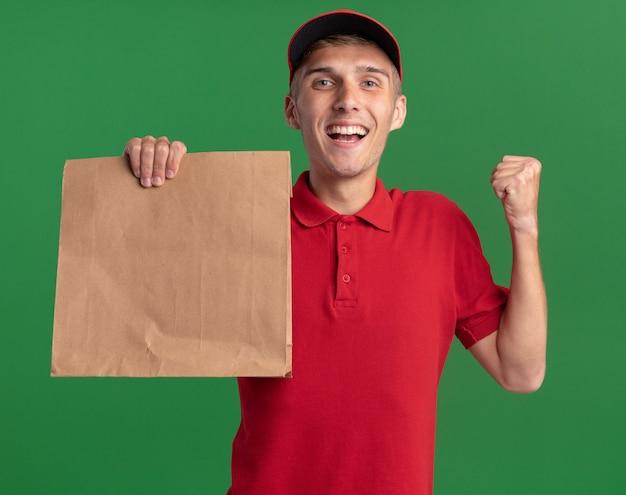 Glücklicher junger blonder lieferjunge hält faust und hält papierpaket