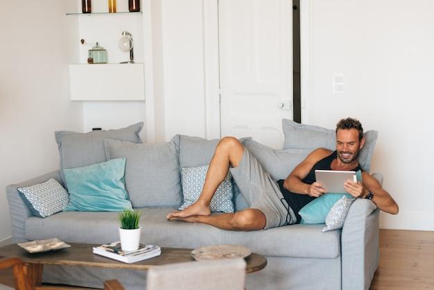 Glücklicher junger blonder mann, der zu hause in der couch auf der tablette sitzt