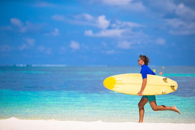 Glücklicher junger brandungsmann, der am strand mit einem surfbrett läuft
