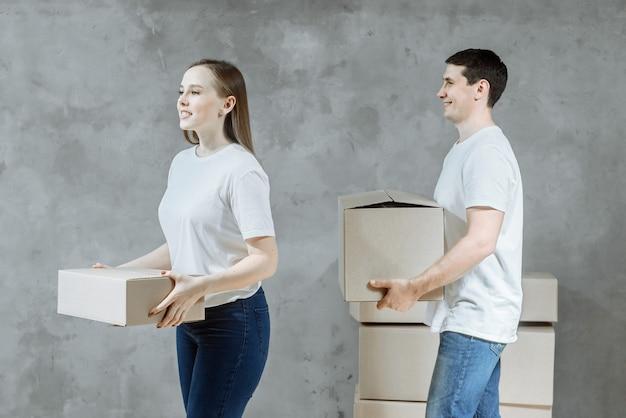 Glücklicher junger ehepaarmann und -frau mit kisten für den einzug nach hause