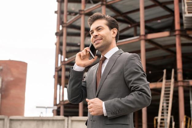 Glücklicher junger eleganter anwalt mit handy, der seinen klienten anruft, um einen termin zu vereinbaren und arbeitsfragen zu lösen