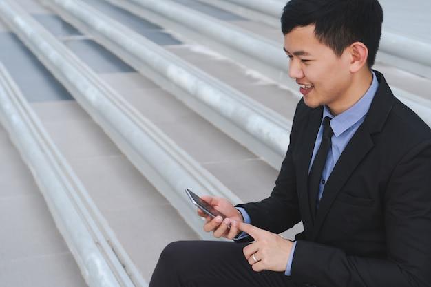 Glücklicher junger erfolgreicher asiatischer geschäftsmann unter verwendung der smartphonelese-e-mail-mitteilung im freien.