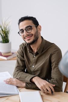Glücklicher junger erfolgreicher männlicher angestellter oder student in der freizeitkleidung, die sie beim lesen des magazins durch tisch betrachtet