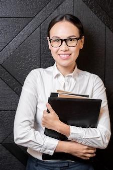 Glücklicher junger erfolgreicher schüler oder lehrer in brille und weißem hemd, die sie beim stehen durch schwarze holzwand betrachten