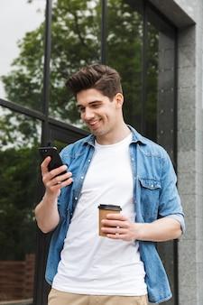Glücklicher junger erstaunlicher mann geschäftsmann posiert draußen draußen zu fuß im chat mit handy kaffee trinken.