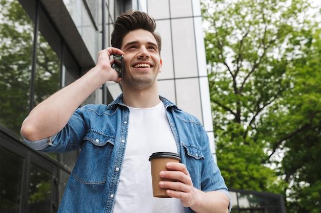 Glücklicher junger erstaunlicher mann geschäftsmann posiert im freien draußen zu fuß und spricht mit dem handy, das kaffee trinkt.