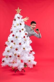 Glücklicher junger erwachsener, der hinter dem geschmückten weihnachtsbaum steht und telefon auf rot hält