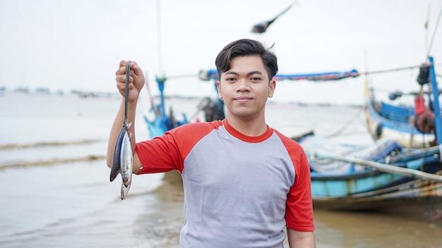 Glücklicher junger fischer am strand, der seinen fangfisch hält und vor seinem boot zeigt
