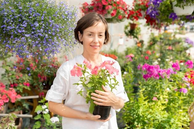 Glücklicher junger florist oder gewächshausarbeiter mit eingetopften petunien, die im gartencenter stehen