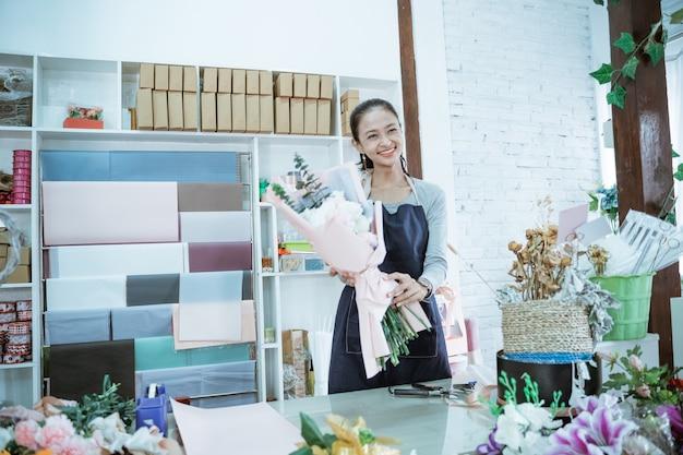 Glücklicher junger frauenflorist, der im blumenladen arbeitet, der flanellblume hält, die front bereit hält, um abzuholen