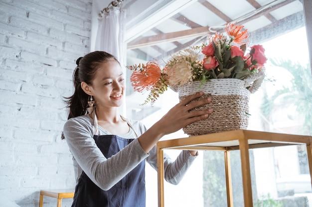Glücklicher junger frauenflorist, der schürze trägt, die eine eimerblume auf tisch in sonnigem tag aufräumt
