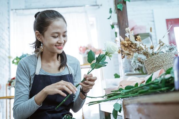 Glücklicher junger frauenflorist, der schürze trägt, die zustandblume allein prüft