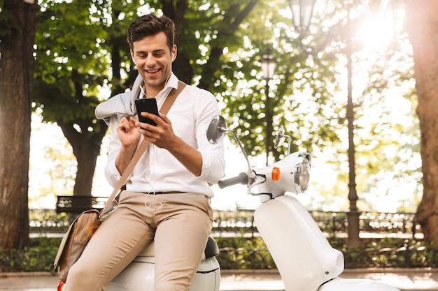 Glücklicher junger geschäftsmann, der auf einem motorrad im freien, unter verwendung des mobiltelefons sitzt