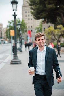 Glücklicher junger geschäftsmann, der auf straße mit seiner digitalen tablette und wegwerfkaffeetasse geht