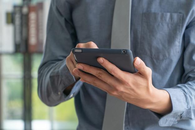 Glücklicher junger geschäftsmann, der digitale tablette verwendet