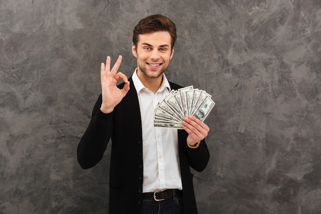 Glücklicher junger geschäftsmann, der geld hält, das okay geste zeigt.