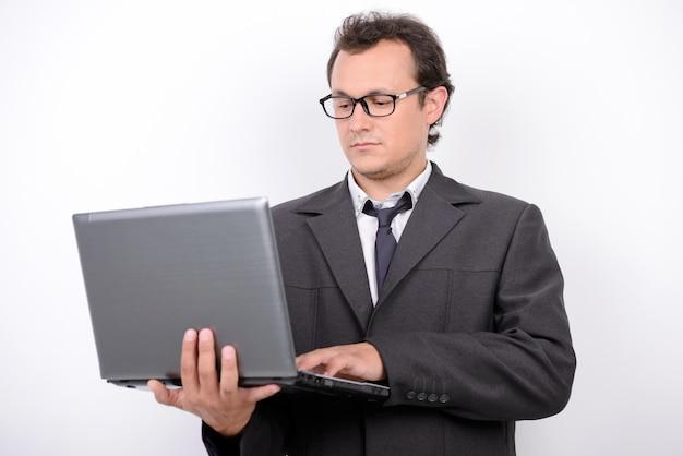 Glücklicher junger geschäftsmann, der laptop-computer und das lächeln hält.