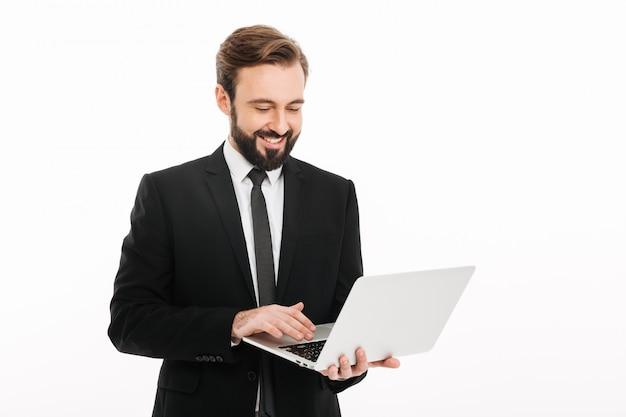 Glücklicher junger geschäftsmann, der laptop-computer verwendet.