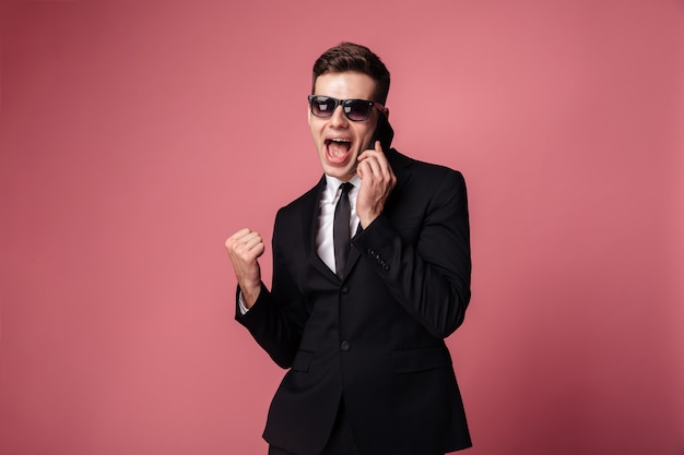 Glücklicher junger geschäftsmann, der per telefon spricht, macht gewinnergeste.
